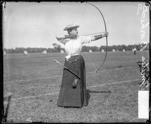 Informal full-length portrait of archer Mrs. Amelia Barhe holding a bow and arrow and pulling back the bow string, standing on an archery field in or near Chicago, Illinois.