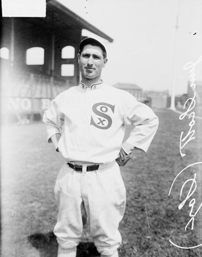 Informal three-quarter length portrait of baseball player Jim Scott of the American League's Chicago White Sox, standing in front of grandstands on the field at Comiskey Park, which was located at 324 West 35th Street and bounded by West 34th Street, South Shield's Avenue (formerly Portland Avenue), and South Wentworth Avenue in the Armour Square community area of Chicago, Illinois. A sign prohibiting betting is visible on a grandstand wall.