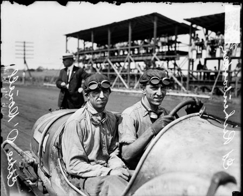 Informal portrait of automobile driver Rickenbacker sitting in the driver's seat of an automobile parked on the side of a road in Elgin, Illinois, during a 1914 automobile race. Automobile mechanic Eddie O'Donnell is sitting in the passenger seat. An unidentified man is standing in the background. A tiered structure is visible across the road in the background.