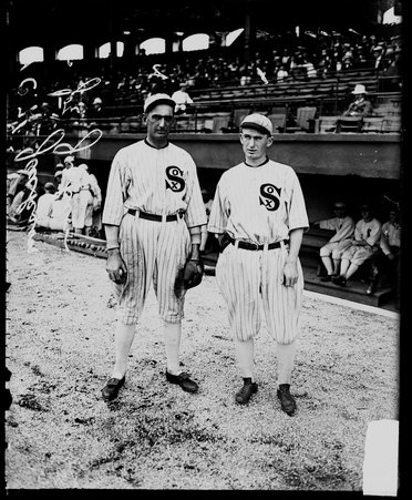 Portrait of American League's Chicago White Sox baseball players Charlie Jackson and Joe Jackson (also known as Shoeless Joe Jackson) standing in front of the White Sox dugout on the field at Comiskey Park, Chicago, Illinois, 1915.