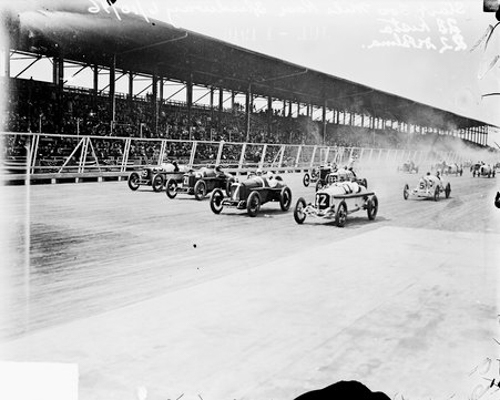 Image of approximately a dozen race cars driving past the grandstands on the race track during the 300 Mile Race at Speedway Park in Chicago, Illinois, 1916. Spectators sitting in the grandstands are visible in the background.