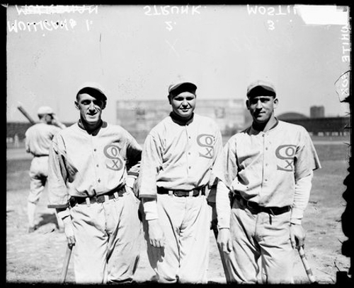 Informal three-quarter length group portrait of baseball players (left to right) Eddie Mulligan, Amos Strunk, and Johnny Mostil, of the American League's Chicago White Sox, leaning on baseball bats that they are holding at their sides, standing on the field at Comiskey Park, which was located at 324 West 35th Street and bounded by West 34th Street, South Shield's Avenue (formerly Portland Avenue), and South Wentworth Avenue in the Armour Square community area of Chicago, Illinois. An unidentified White Sox player holding a baseball bat is standing in a batting stance in the background.