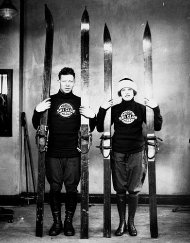 Full-length portrait of Norge Ski Club skiers Carl Nelson and Miss Margaret Thompson holding skis and ski poles, standing in front of a light-colored backdrop in a room in Chicago, Illinois.