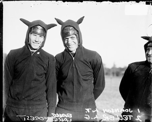 Half-length portrait of Lake Forest football players Tellers and Johnson standing on an athletic field in Lake Forest, Illinois; 1924. They are wearing sweat suits with fabric horns on the hoods for their team mascot, the Devils. A teammate is partially visible on the right side of the image.