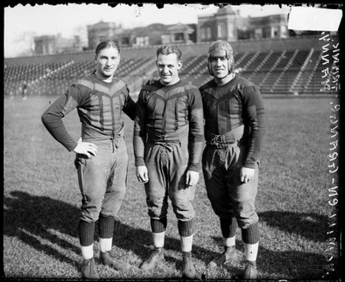 Chicago Bears football players Harold Red Grange, Frank Hanny, and McMillen at Weeghman Park, Chicago, Illinois, 1925. Weeghman Field was renamed Wrigley Field in 1927.