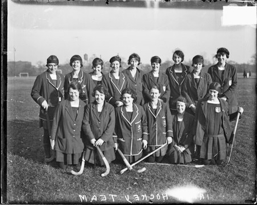 Informal portrait of members of the Irish women's field hockey team kneeling and standing in two rows on a grass field in or near Chicago, Illinois.
