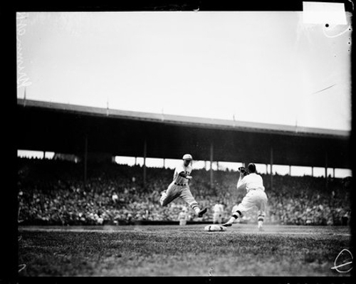 Unidentified baseball player of the New York Giants, leaping towards first base during a game against the Cubs at Wrigley Field, Chicago, Illinois, 1926. Cubs first baseman, Grimm, is standing at first base.