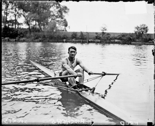 Informal portrait of rower Fred Riechers sitting in a racing shell in a body of water in Chicago, Illinois, holding on to oars.