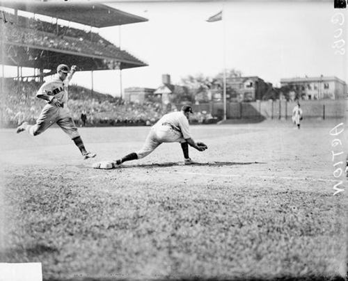 Unidentified Chicago Cubs baseball player lunging to catch ball at first base as unidentified Boston Braves baseball player reaches the base at Wrigley Field, Chicago, Illinois, 1929.