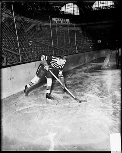 Full-length portrait of Chicago Black Hawks ice hockey player Johnny Gottselig holding a hockey stick next to a puck, dark exposure, standing on an ice rink in a sports arena in Chicago, Illinois. A sign in the backgrounds reads: Please Do Not Smoke.