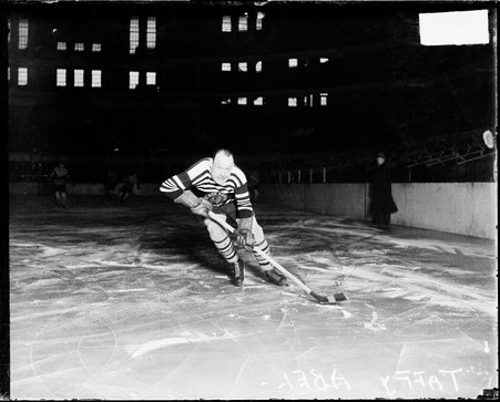 Full-length portrait of Chicago Black Hawks ice hockey player Taffy Abel skating on an ice rink in a sports arena in Chicago, Illinois, holding a hockey stick.