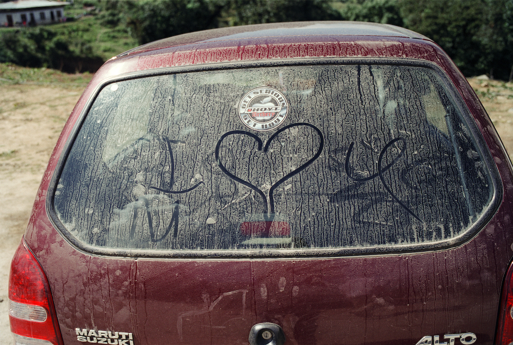 A car with I love you written in dirt on th rear view mirror in the Punakha valley, Bhutan.