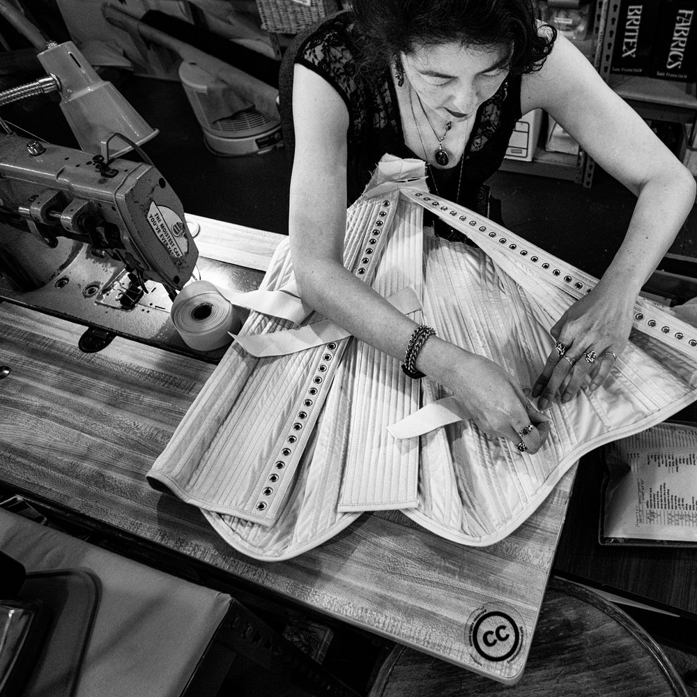 Cat Woish at Dark Garden working on a fully boned bespoke leather corset.