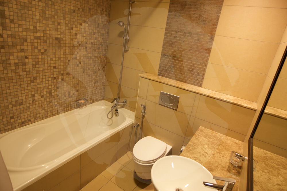 The bathroom is spacious with bath and shower, large sink area with huge wall-mounted mirror