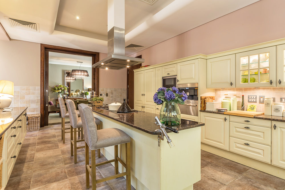 Generous family kitchen with coffee machine, several fridges and breakfast bar
