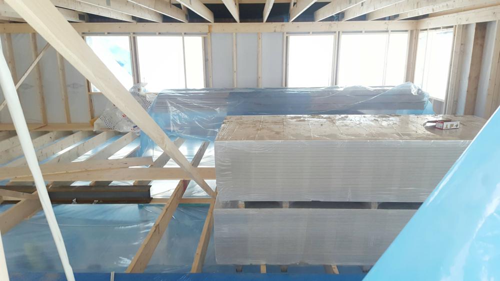 Plasten över ett fönster på övervåningen hade släppt, så vi kunde kika in innan vi tejpade fast den. Här ser man att hela nedervåningen är inplastad för att luftavfuktaren mer effektivt ska torka ut betongplatta och syllar.