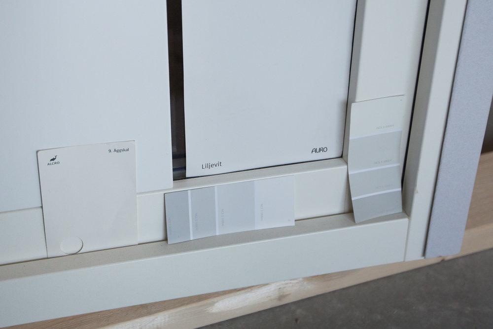 Testar vilka vita/grå kulörer som matchar med fönstrens och innerdörrarnas Stockholmsvita (NCS S 0502-Y)som vi får utgå ifrån. Att få en annan kulör på fönstren invändigt och alla innerdörrar gick påöver 30.000 kr, så det var bara att glömma.