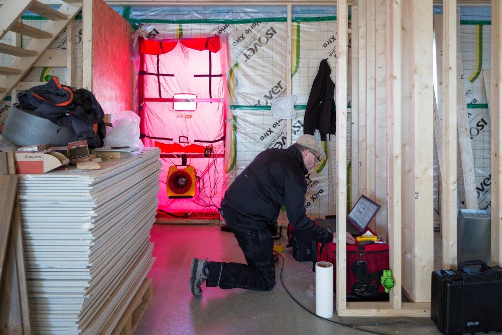 En dörröppning täcks med en lufttät duk med hål för fläkten som skapar ett undertryck i huset. Innan detta har alla ventiler, avlopp,radonrör etc tejpats igen.