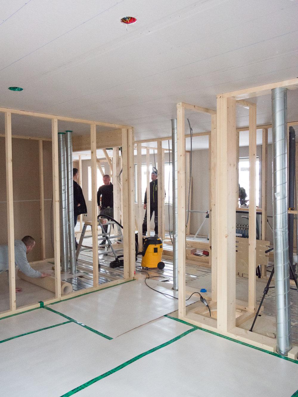 Andreas stämmer av läget med snickarna. Vy från master bedroom med walk in closet till vänster och badrum med bastu till höger.