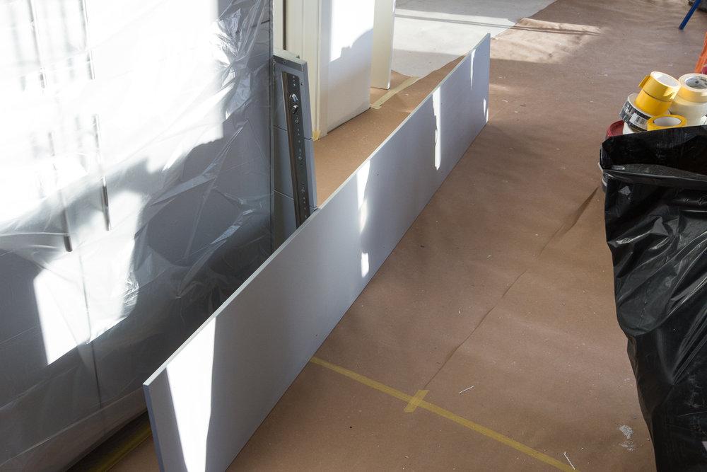 IKEA VEDDINGE täcksida (grå NCS-S 2502B) som ska sitta under väggskåpen.