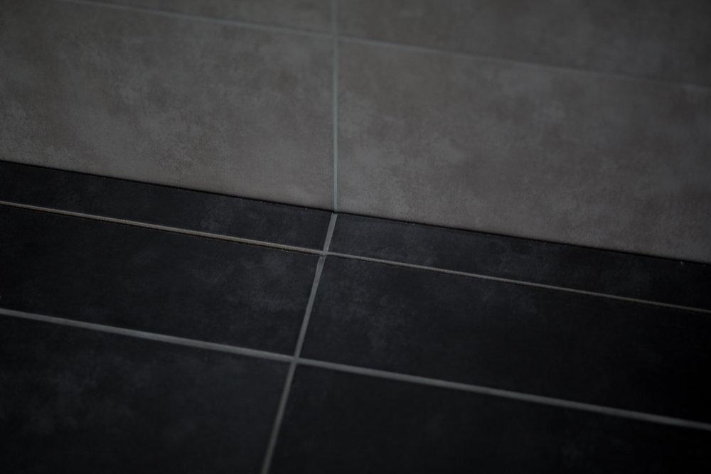 Osynlig golvbrunn  Unidrain HighLine (sponsor).  Genom en springa mellan klinkerplattorna rinner vattnet ner. Med denna slipper vi även gå ner i storlek på klinkern och kan ha 60x60 cm i hela badrummet.