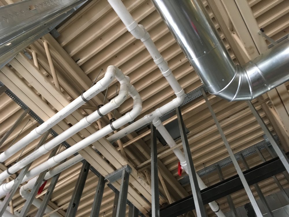 Vapor mitigation system installed ceiling piping (during installation) and extraction point control valves in a remodeled commercial space