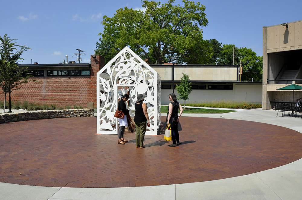 This is NOT a Refuge    Site-specific installation at Kansas City Art Institute Rowland Plaza, 2018   Laser cut, powder coated, aluminum steel plate  12' height x 10' depth x 8' width, 4' x 18' wood bench inside   Artist Description