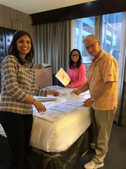2020 Mom team stuffing registration folders. (Vrinda Devani, MD, board member; Millie Pagett, RN volunteer; Ed Pagett, volunteer and advocacy team member)