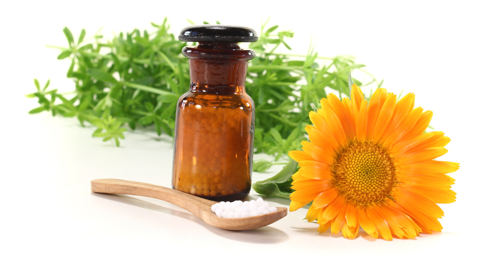 homeopathic medicine bottle and flower