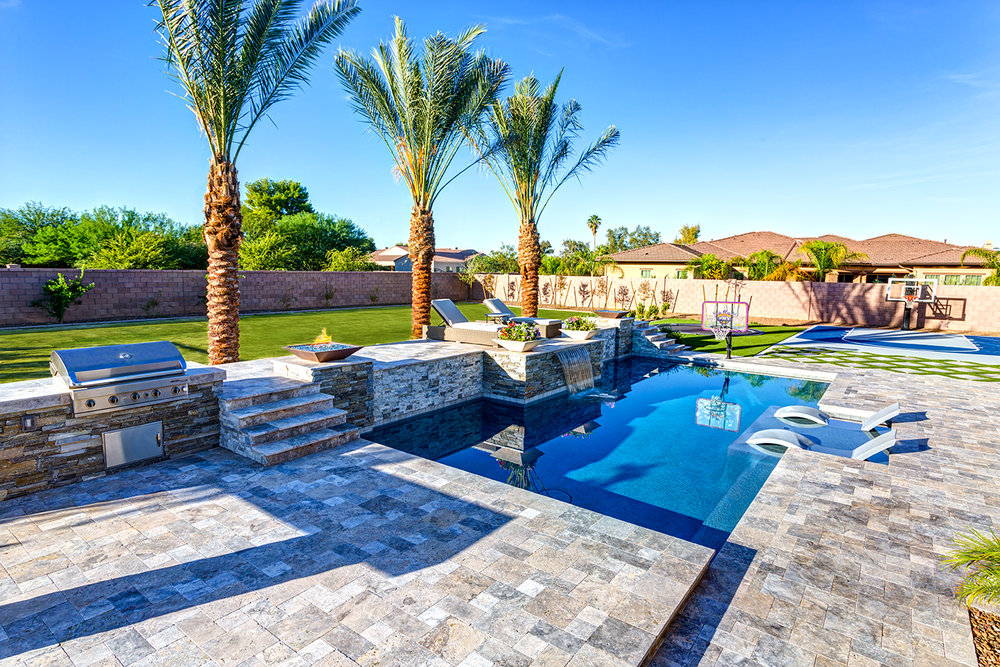 The first pool features beautiful aspects from the outdoor living department. The geometric pool design is complimented by an outdoor grill and basketball court. The family chose to add a baja step, waterfall, and multiple fire pits to finish off the design.