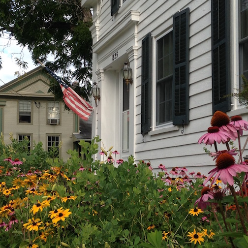 Cone flowers and black-eyed Susan enliven the front of this greek revival cottage in Essex, NY