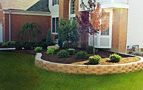 Mulched area surrounded by tan bricks elevated above a green yard - Premier Lawn Care Nashville