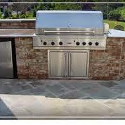 Outdoor gas grill surrounded by a custom brick cabinet on a stone patio - Premier Lawn Care Nashville