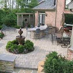 Custom brick patio with stone steps, outdoor seating and fountain - Premier Lawn Care Nashville