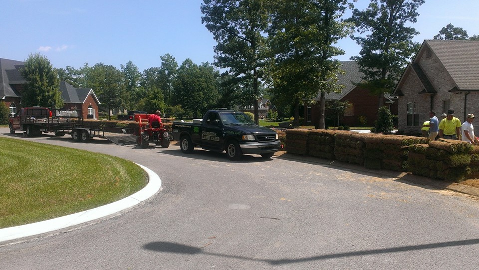 Landscaping company truck and workers in a housing development unloading sod - Premeri Lawn Care Nashville