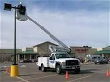 Large white truck working on a parking lot light in a strip mall - Premier Lawn Care Nashville