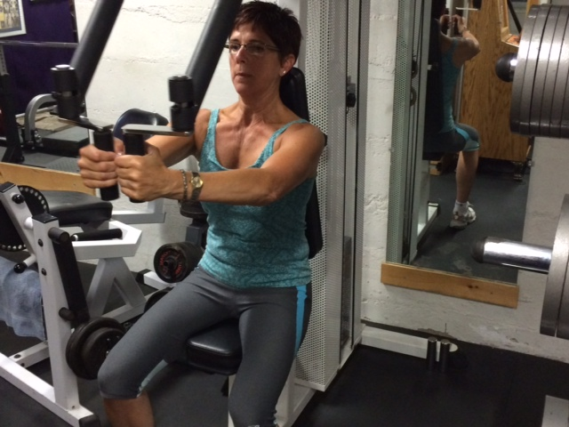 Claudette, working her chest muscles using the pec-dec machine