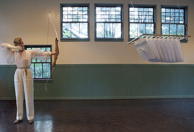 Mitchell performs her piece, One Shot, shooting a single arrow through sheets of paper where it stays, suspended.