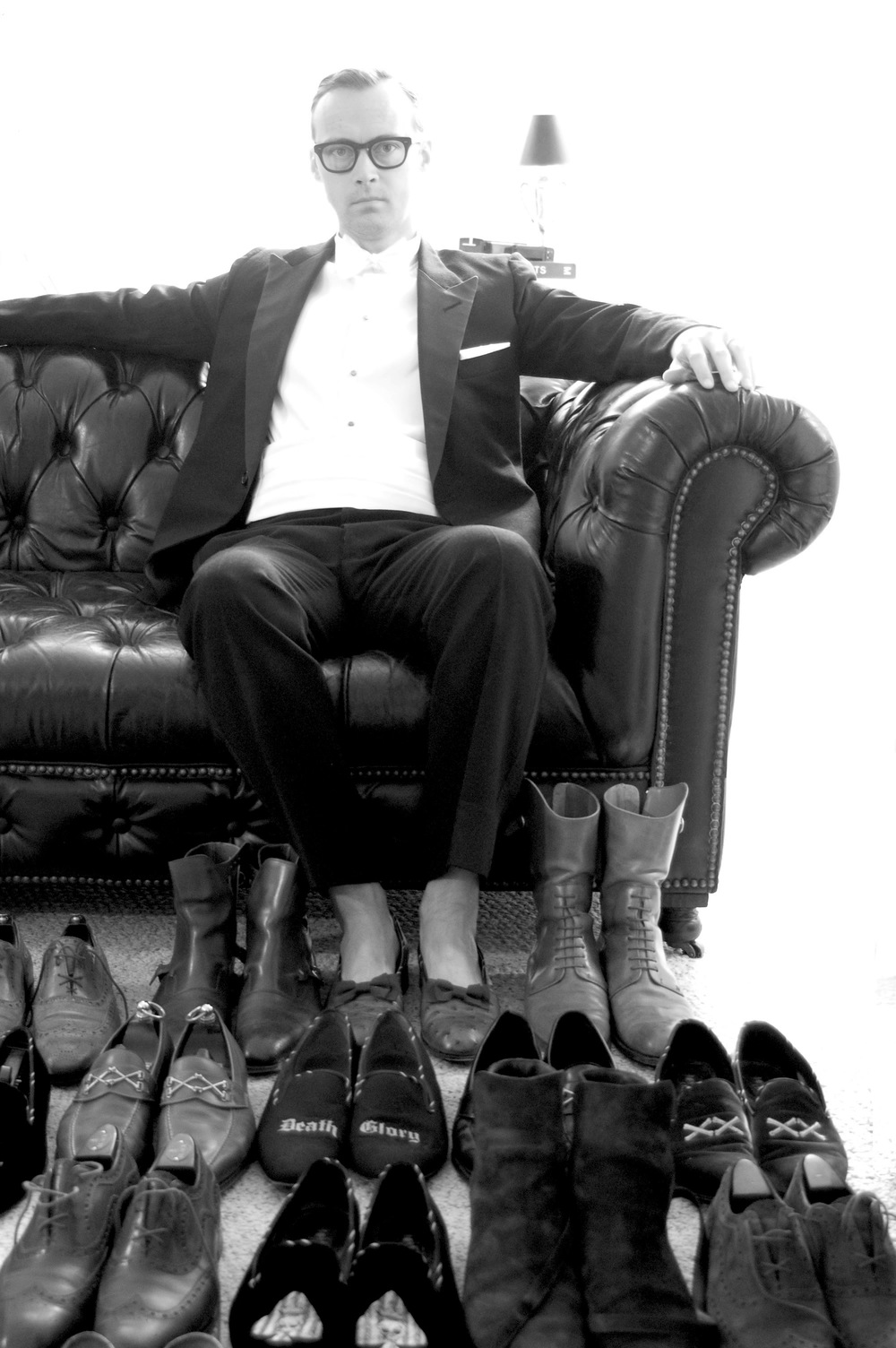 Derrick Miller black-tie lounging amongst a selection of his Barker Black footwear.