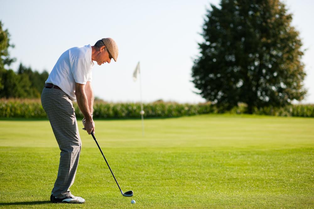 Older golfer chipping a golf ball onto a green