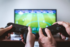 Two players hold PlayStation 4 controllers while playing a game via Pexels