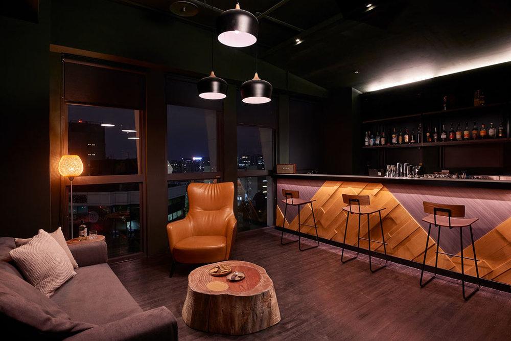 隱身於活動區後方的吧台作為工作人員休憩使用,橘黃燈光搭配陳列窖中美酒無不令人陶醉|圖片來源:Kafnu 官方網站