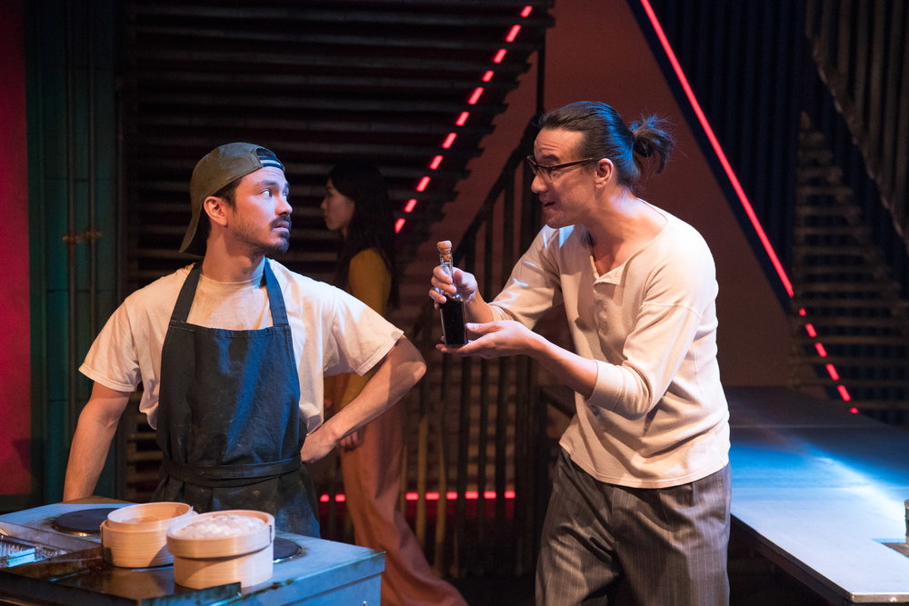 Street Hawker ( Andy Kettu ) and Leung ( Matthew Leonhart ) in '  Mountains: The Dreams of Lily Kwok  ' performed at the   Royal Exchange Theatre   (22 Mar - 7 Apr 18) ||  Photo by    Jonathan Keenan   - courtesy of the Royal Exchange Theatre
