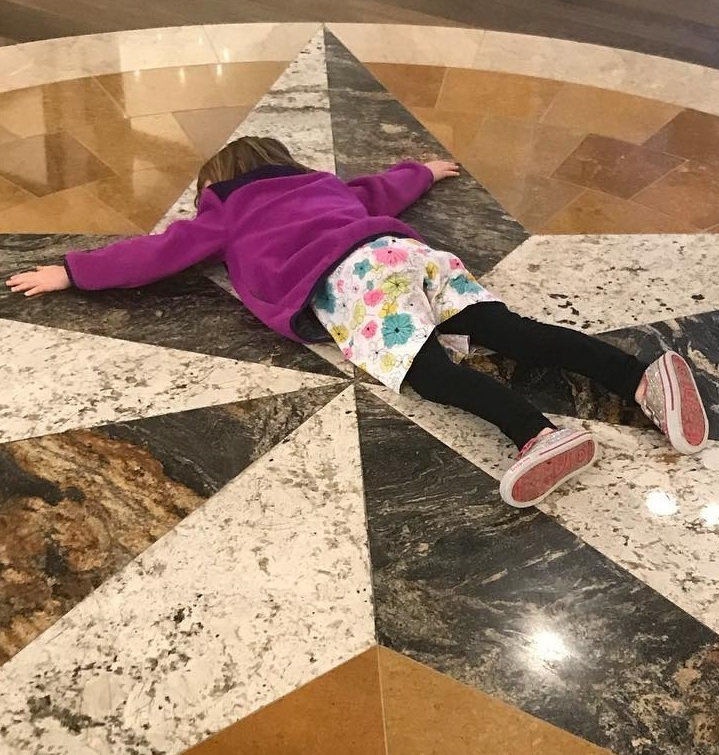 Because the bank floor is a good place to lay down.  [Image description: four year old white child with light brown hair laying face down in the middle of a star etched onto the floor of a bank]