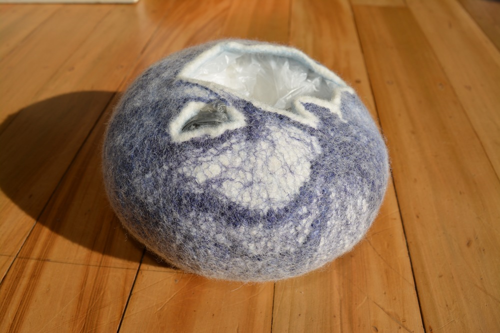 Felted bowl stuffed with plastic carrier bags during drying