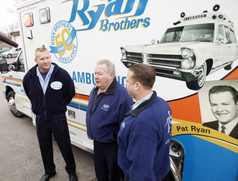 Pat Ryan, center, talks about the business that he and his brother, Paul Ryan, started in 1962. Pat's sons, Erin, left, and Patrick, right, surprised him on Monday with a commemorative ambulance to mark the firm's 50th anniversary.