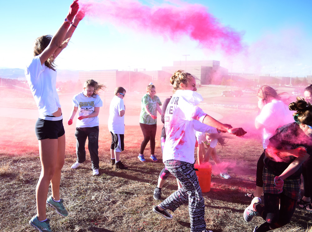 Senior Abby Suntken jumps with pink powder in her hands during the color fight.