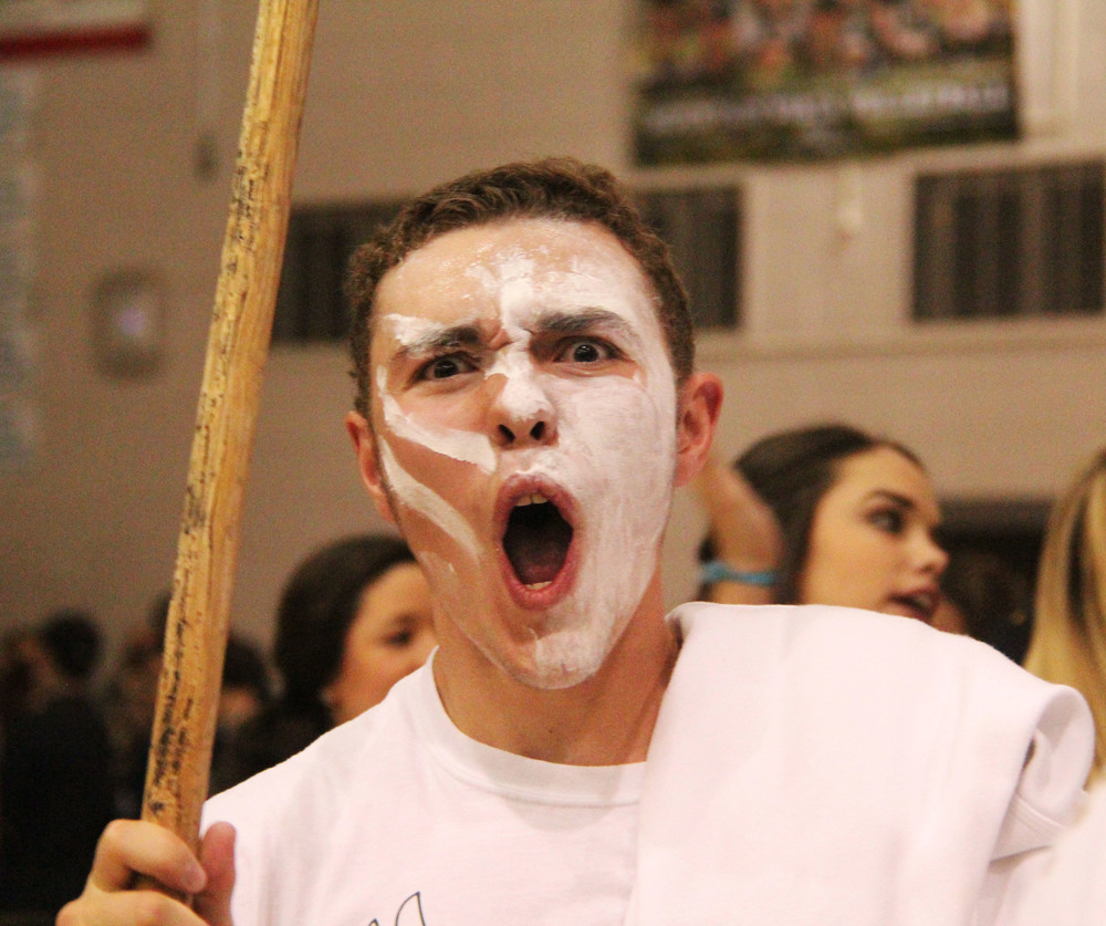 Junior Paxton Boyer, decked in white,looks at a camera before the junior boys' poms dance during 2014 Homecoming Week.