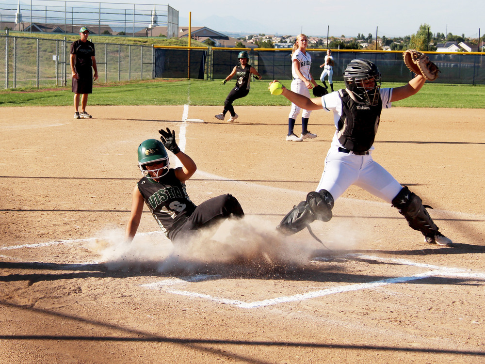 Freshman Rebecca Gonzales slides in home as ThunderRidge's catcher tries to salvage the out at first base.