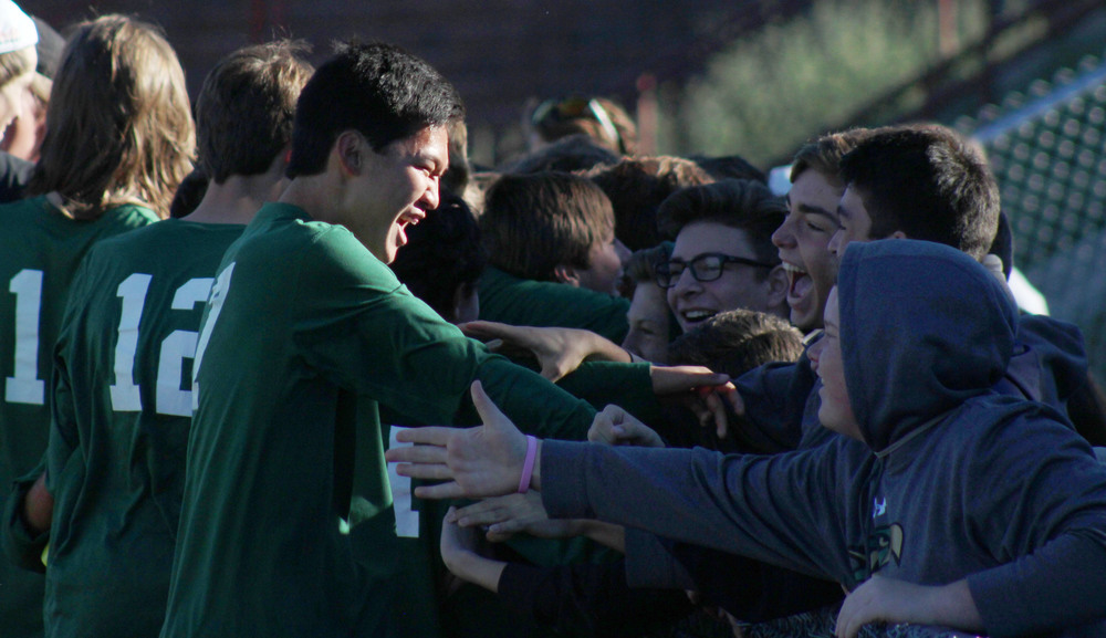 Junior Nolan Gao rushes to the fence to greet his friends following the upset.